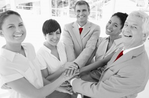 Cheerful smiling businesspeople performing teamwork gesture